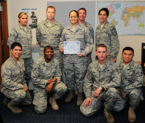 Staff Sgt. Mellissa Seumanu (center) stands with her peers after being awarded Andersen's Best here Dec. 16. As 36th Logistics Readiness Squadron deployment manager, Sergeant Seumanu ensures the 36th Wing quickly fills all Air Expeditionary Force taskings providing Pacific Air Power from Andersen Air Force Base. Andersen's Best is a recognition program which highlights a top performer from the 36th Wing. (Photo illustration/Senior Airman Nichelle Anderson)