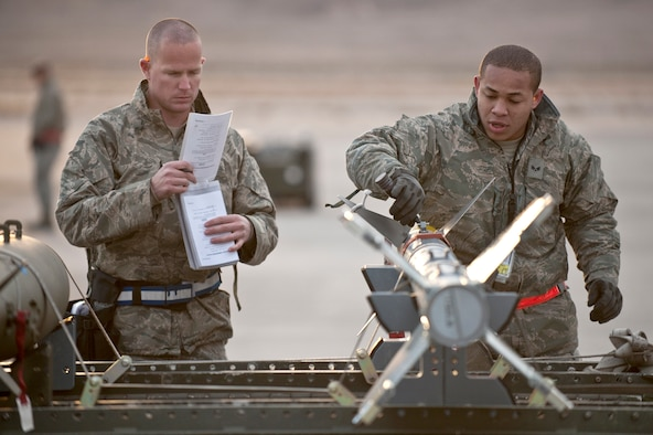 Senior Airman Eric Arrington and Senior Airman Keli Manglona go over a pre-load checklist on an AIM-9 air-to-air missile during a weapons load competition Jan. 7, 2011, at Nellis Air Force Base, Nev. Weapons load competitions are conducted quarterly to keep Airmen sharp and recognize superior performers. Weapons load teams are evaluated for their use of the checklist, safety and overall speed. Both Airmen are assigned to the 57th Aircraft Maintenance Squadron as aircraft armament systems journeymen. (U.S. Air Force photo/Tech Sgt. Michael R. Holzworth)