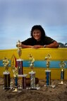 """Master Sgt. Diane (Dee) Marques, 48th Aerial Port Squadron Air Transportation Craftsman sits on the beach with her surfboard and the trophies she has earned over the years. Sergeant Marques uses surfing as a means of fitness as well as relaxation. """"Surfing is about laughing at yourself when wiping out on a wave,"""" she said. """"It's when you have a stressful day at work and you think about surfing to get away, no phone calls, peacefulness and waiting with friends at the line up to catch a wave."""" (U.S. Air Force photo/Staff Sgt. Erin Smith)"""