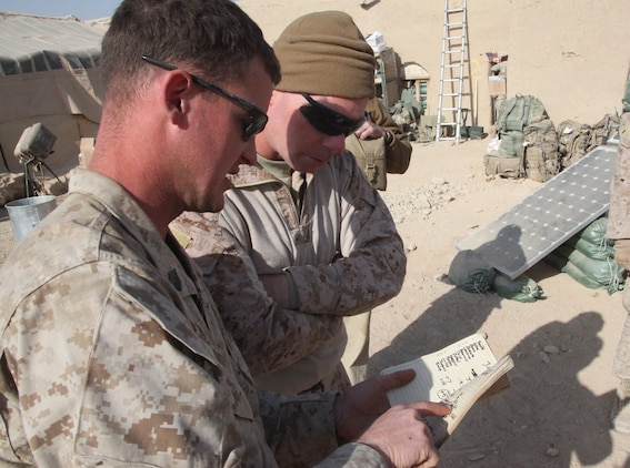 """Sgt. David Doty, a squad leader with 1st Platoon, India Company, 3rd Battalion, 5th Marine Regiment, shows his platoon's solar energy data to Maj. Sean Sadlier, the Expeditionary Energy Liaison Officer, with Regional Command Southwest, at Patrol Base Sparks in Sangin District, Dec. 29. The Marines and sailors of 'I' Company, 3/5, have been testing the Experimental Forward Operating Base solar energy devices since pre-deployment training in July. """"Our generators typically use more than 20 gallons of fuel a day. We are down to 2.5 gallons a day,"""" said Doty, a Fulton, Mo., native. """"The system works amazing. By saving fuel for generators, it has cut back on the number of convoys, meaning fewer opportunities for one of our vehicles to hit an IED."""""""