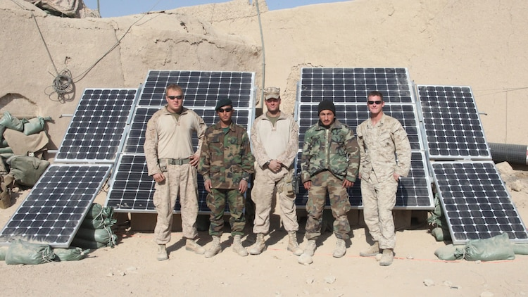 """Marines and sailors of India Company, 3rd Battalion, 5th Marine Regiment, and their Afghan national army counterparts, pose in front of a modified ZeroBase Regenerator at Patrol Base Sparks, in Sangin District, Dec. 29. The ZeroBased Regenerator, nicknamed """"the Raptor,"""" after the type of power cells in its six solar panels, can keep more than 17 computers and 15 lighting units running throughout the night. The Marines of 1st Platoon, added four more panels to their """"Raptor"""" for further solar energy conservation."""