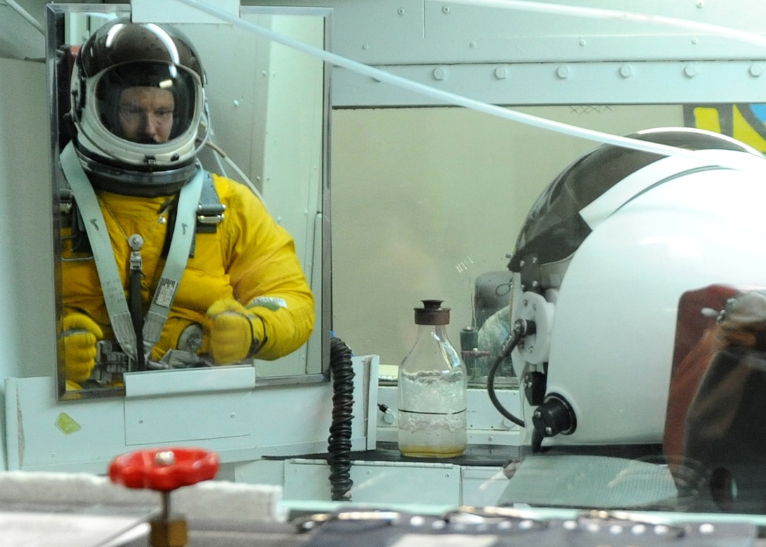 Gen. William M. Fraser III, commander of Air Combat Command, looks in the mirror as he tenses up while ascending in the high-altitude chamber at Beale Air Force Base, Calif., Jan. 10. The ascent to 70,000 feet causes the pressure suit to inflate, keeping the body at an altitude of 35,000 feet. (U.S. Air Force photo/9th Reconnaissance Wing Public Affairs)