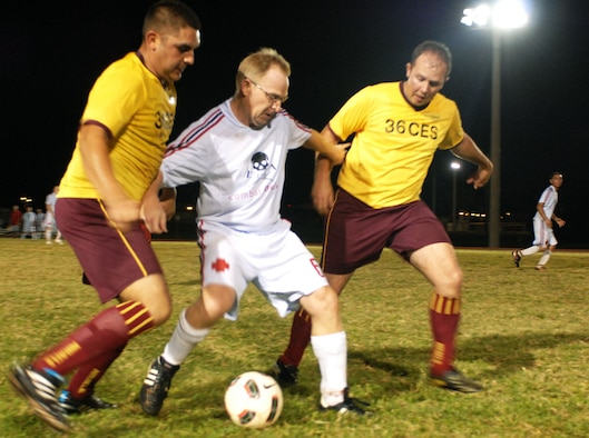 A 36th Medical Group team member defends the ball against two 36th Civil Engineer Squadron players during the 2010 Intramural Soccer Championship game, here Jan. 10. The Med Group defeated the CE team 3-1. (U.S. Air Force photo/ Airman 1st Class Anthony Jennings)