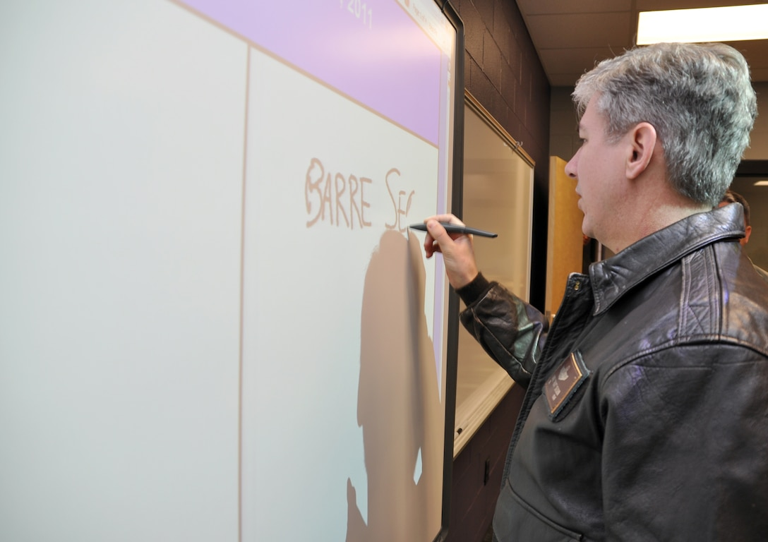 """Col. Barre Seguin, 14th FTW commander, takes a turn at writing on one the new Columbus Middle School's """"smart boards"""" Jan. 13 during a tour of the facility. Each classroom in the newly constructed facility houses one of these interactive boards that allow teachers a multitude of innovative tools to instruct with. (U.S. Air Force photo/Staff Sgt. Jacob Corbin)."""