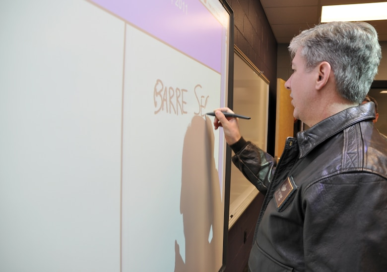 "Col. Barre Seguin, 14th FTW commander, takes a turn at writing on one the new Columbus Middle School's ""smart boards"" Jan. 13 during a tour of the facility. Each classroom in the newly constructed facility houses one of these interactive boards that allow teachers a multitude of innovative tools to instruct with. (U.S. Air Force photo/Staff Sgt. Jacob Corbin)."