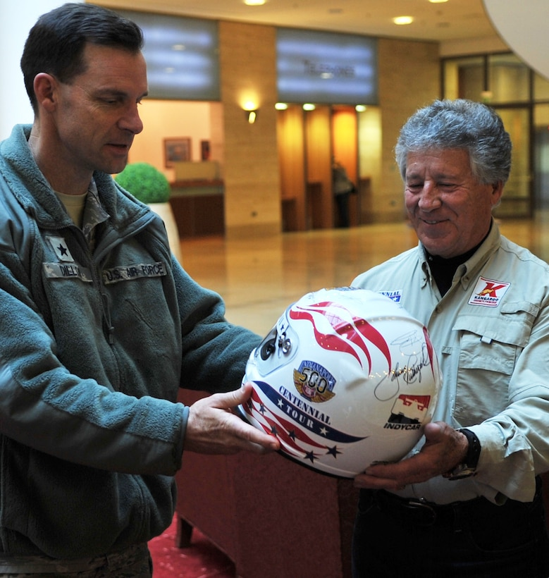 Brig. Gen. Mark Dillon receives an autographed helmet from Mario Andretti, an Indy 500, Daytona 500 and Formula 1 champion, during the Indy 500 Centennial Tour, Jan. 14, 2011, at Ramstein Air Base, Germany. The Indy 500 Centennial tour brings Indy racing teams to Europe and the Middle East over a 10-day tour to honor and boost morale for service members and their families. General Dillon is the 86th Airlift Wing commander (U.S. Air Force photo/Senior Airman Caleb Pierce)