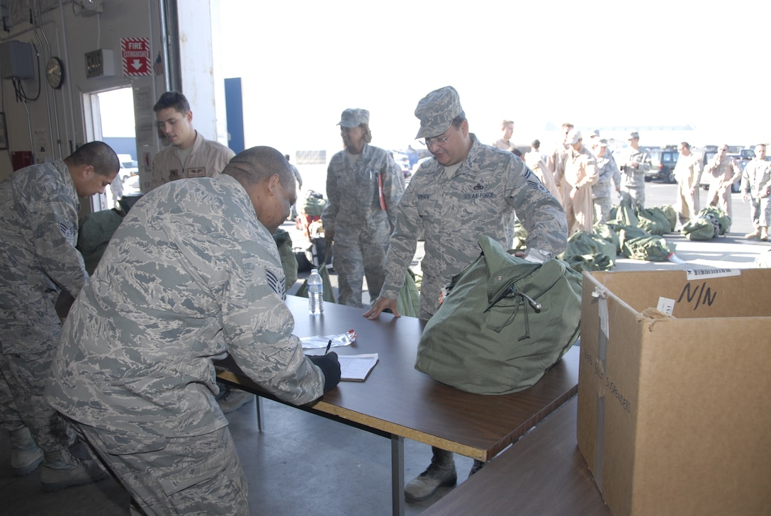 Members from the 129th Logistic Readiness Squadron's Material Management Flight, 129th Rescue Wing, Moffett Federal Airfield, Calif. assist Airmen turning in mobility bags after redeploying from overseas, Jan. 12, 2011. (Air National Guard photo by Tech. Sgt. Ray Aquino)
