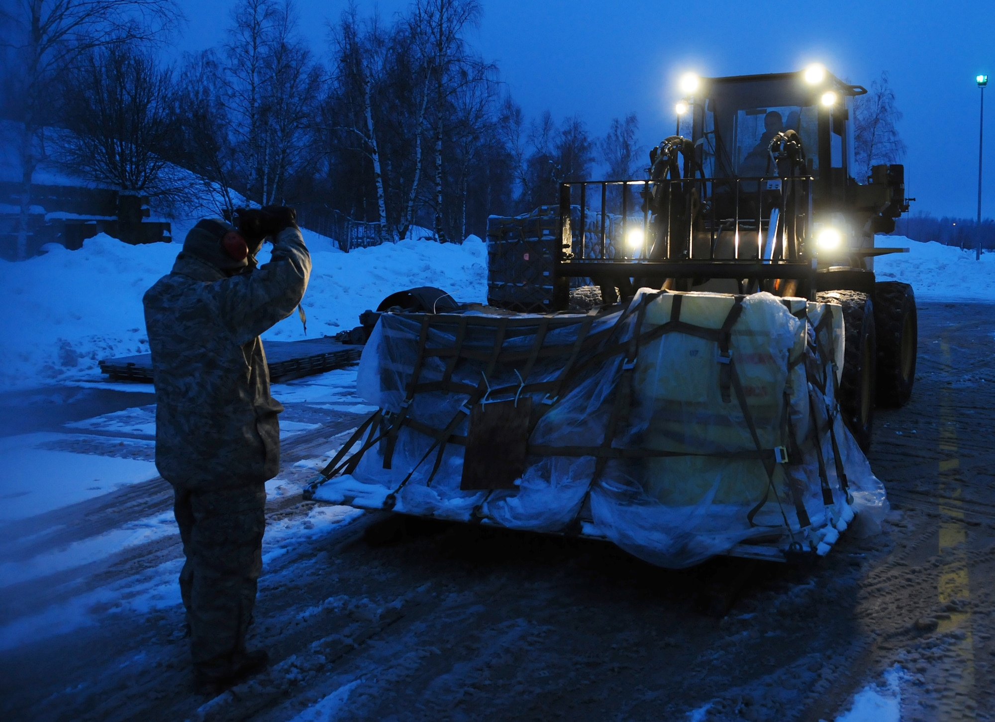 Tech. Sgt. Carlos Cardenas guides a forklift being driven by Senior Airman Scott Knight Jan. 7, 2011, at Lithuania Air Force Air Base in Lithuania. Sergeant Cardenas and Airman Knight are assigned to the 493rd Expeditionary Fighter Squadron Redeployment Action Team at Royal Air Force Lakenheath, England. (U.S. Air Force photo/Staff Sgt. Stephen Linch)