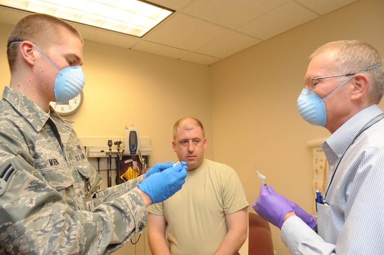 Buckley Air Force Base, Colo.-  Dr. Thomas Hadduck and Airman 1st Class Josh Moen, 460th Med Group,  prepares a shot , Jan 19, 2011. Dr. Hadduck and Airman Josh Moen were recognized during the 460th Med Group inspection for a medical procedure performed during the inspection.   ( U.S. Air Force Photo by Airman First Class Marcy Glass )