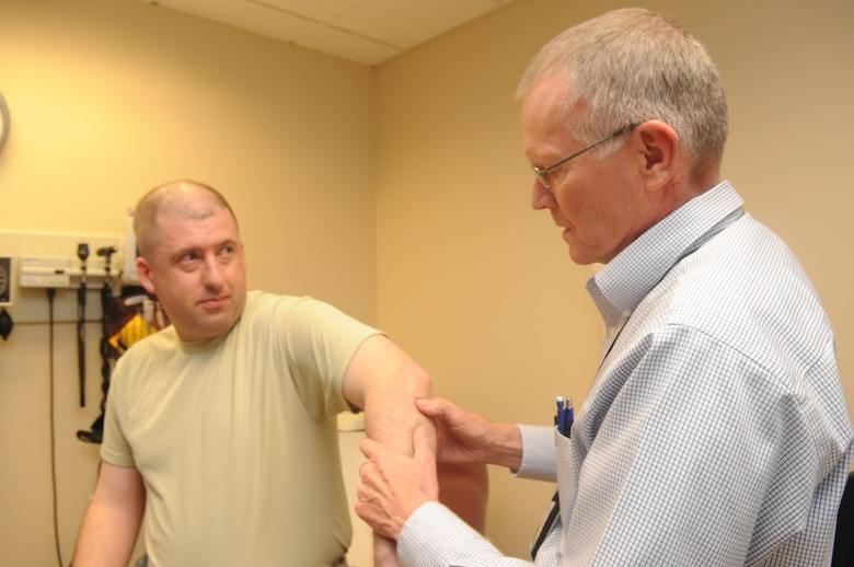 Buckley Air Force Base, Colo.-  Dr. Thomas Hadduck, 460th Med Group,  examines a patient's arm during a follow up, Jan 19, 2011. Dr. Hadduck was recognized during the 460th Med Group inspection.   ( U.S. Air Force Photo by Airman First Class Marcy Glass )