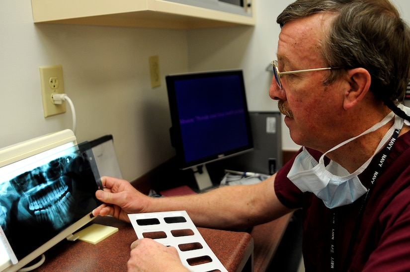 Navy Capt. Dr. William Reynolds (retired) checks a patient's x-rays prior to an examination at Naval Health Clinic Charleston Dental, Jan. 13. An x-ray can tell a doctor if there are problems with a patient's jaw and show cavities or other issues concerning the teeth. (U.S. Navy photo/Mass Communication Specialist 1st Class Jennifer R. Hudson)