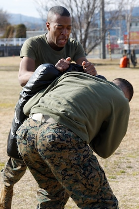 Pfc. Samuel Jordan, a station food service specialist, knees a punching pad during an oleoresin capsicum course at the Provost Marshal's Office here Jan. 20. The participating service members were required to effectively attack and defend themselves during the obstacle course after being sprayed in the eyes with OC spray.