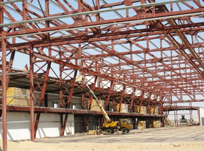 An Iraqi construction crew unloads pallets of equipment for the aircraft maintenance hangar in Taji.  The massive aircraft hangar is a $9.8 million project that began in 2009. (Courtesy photo)
