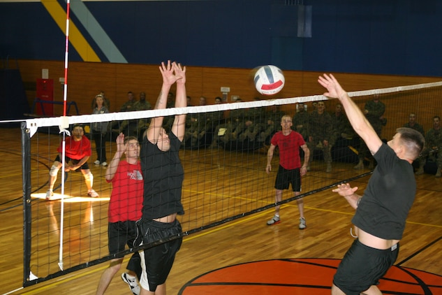 Michael Salinas (left), Combat Logistics Company 36 volleyball player, throws up both hands while leaping in anticipation of Matthew Lowry's, Marine Aviation Logistics Squadron 12 volleyball player, spike during the Commander's Cup Volleyball Single Elimination Challenge at the IronWorks Gym sports courts here Jan. 21. Salinas proved critical to CLC-36's comeback against MALS-12 in the championship match.