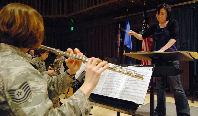 """Chie Imaizumi, right, conducts during a rehearsal of her musical piece, """"Opening New Doors,"""" while Tech. Sgt. Julia Taylor, left, plays flute. """"Opening New Doors"""" is the first piece Ms. Imaizumi, a native of Saitama, Japan, has composed for an orchestral band. Sergeant Taylor, a native of Telford, Penn., performs for the Air Force Academy Band's marching and concert bands and Academy Winds ensemble. (U.S. Air Force photo/Staff Sgt. Don Branum)"""