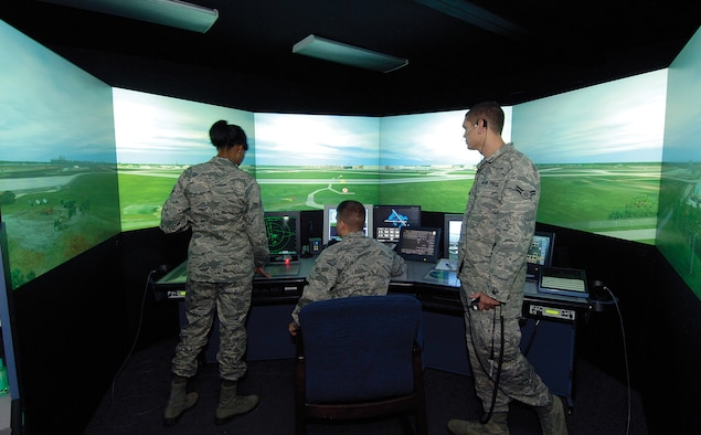 Located at the foot of the Air Traffic Control Tower, the training simulator is a 360-degree Tinker virtual tower. Lead by instructors through customized events, the trainees learn Tinker-specific language, aircraft and scenarios that acclimate the Airmen to the real world high above. Training, in the tower and in the simulator, may take up to a year before the Airman is rated. (Air Force photos by Margo Wright)
