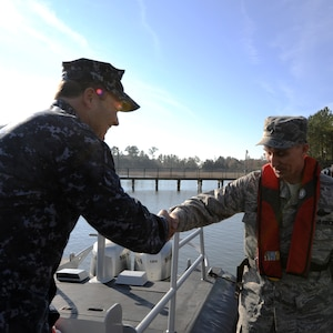 Navy Chief Warrant Officer 3 John WIlson welcomes Brig. Gen. William Bender, commander, United States Air Force Expeditionary Center, onboard a patrol boat at Joint Base Charleston - Weapons Station, Jan. 20. General Bender visited JB CHS for the first time after the realignment of the 628th Air Base Wing under the U.S. Air Force Expeditionary Center.