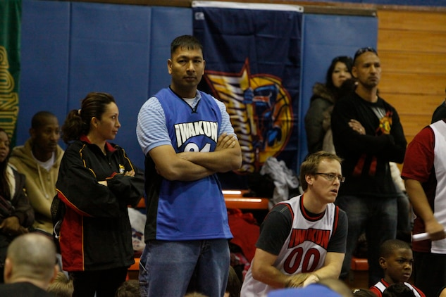 Justin Josxi, Team 3 for the 7 to 9-year-old division head coach, awaits for his team to be introduced during the opening ceremonies here Jan. 22. Josxi anxiously awaits practicing with his team to teach them the team work basketball can bring.