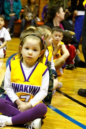 Maya Walters, number 7 for 5- to 6-year-old division Team 2, sits with the rest of her team before they are introduced at the opening ceremonies here Jan. 22. Walters and her team mates were excited to start playing their favorite sport.