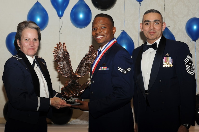 Col. Martha Meeker, left, and Chief Master Sgt. Jose LugoSantiago, right, presents Airman 1st Class Deaven Gathers with the Airman of the Year award for 2010 during the annual awards banquet held at the Charleston Club Jan 20, 2010. Airmen, Sailors and civilians were presented with an award for their outstanding accomplishments from one of the 15 different categories recognized. Unable to attend the banquet due to deployment or other reasons was, from the 628th Mission Support Group, Noncommissioned Officer of the Year Staff Sgt. Akeem Parks; from the 628 MSG, Senior Noncommissioned Officer of the Year Master Sgt. Michael Patterson; from the 628 MSG, First Sergeant of the Year Master Sgt. Steven Hart; and from the Naval Weapons Station, Sailor of the Year Personnel Specialist 1st  Class Petty Officer James Long. Colonel Meeker is the Joint Base Charleston commander, Chief LugoSantiago is the 628th Air Base Wing command chief and Airman Gathers is from the 628 MSG. (U.S. Air Force photo/Tech. Sgt. Chrissy Best)