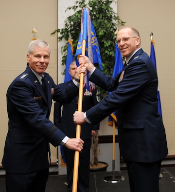 SCOTT AIR FORCE BASE, Ill. -- Gen. William Shelton, commander of Air Force Space Command, presents the Air Force Network Integration Center guidon to its new commander, Col. Curtis Piontkowsky, during a change of command ceremony Jan. 26. AFNIC is the Air Force's focal point to shape, provision, sustain and integrate the AF enterprise network and enable assured core cyber capabilities to achieve warfighting advantage. (U.S. Air Force photo/ Airman 1st Class Divine Cox)