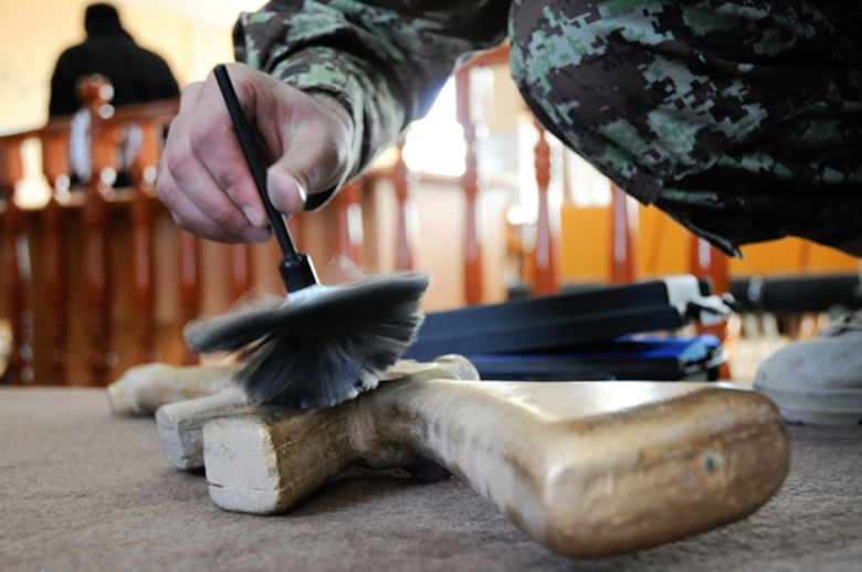 HERAT, Afghanistan -- An Afghan National Army military policeman dusts a mock M-16 rifle for finger prints during a training scenario at Camp Zafar, Herat Province, Afghanistan, Jan. 17, 2011. Dusting for prints was one of many skills that 12 ANA officers learned during the first-ever ANA two-week Criminal Investigation Basic Course, which graduated Jan. 19. (U.S. Air Force photo/Airman 1st Class Lausanne Morgan)