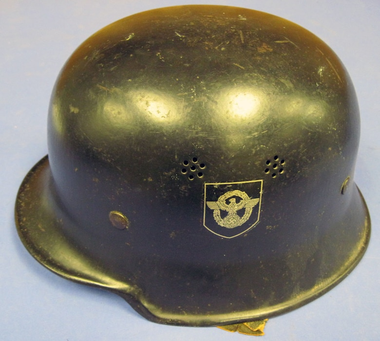 This helmet has the German police (Deutsch Polizei) and National Socialist Party (Nazi) decals and includes a leather neck cover. The German Police used this type of light-weight helmet during regular duty in hazardous situations. (U.S. Air Force photo)