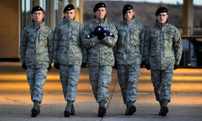 A cadet honor guard conducts reveille Jan. 28, 2011, carrying a flag that survived the explosion of the Space Shuttle Challenger 25 years ago that day. The honor guard is composed of cadets who are Eagle Scouts. (U.S. Air Force photo/Rachel Boettcher)
