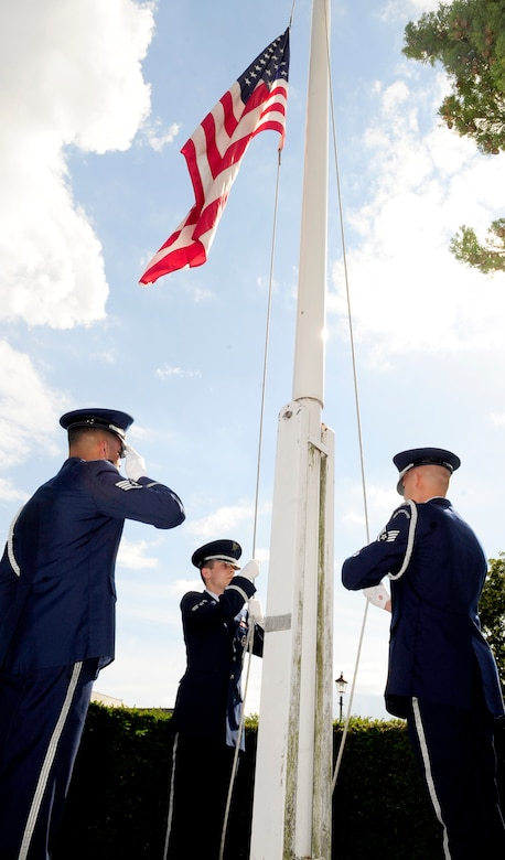 RAF MILDENHALL, England – Staff Sgt. Emmanuel Santillan, Airman 1st Class Taylor Mogford and Senior Airman Zachary Kruly, all RAF Mildenhall Honor Guard, perform flag security detail during retreat here July 1, 2011. Retreat signals the end of the duty day, while also paying respect to the flag. (U.S. Air Force photo/Senior Airman Ethan Morgan