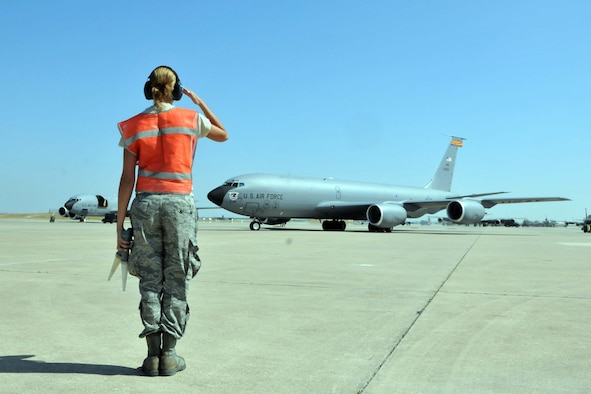 "Airman 1st Class Kristin Love renders a hand salute after marshalling a KC-135 ""Stratotanker"" off the parking ramp prior to