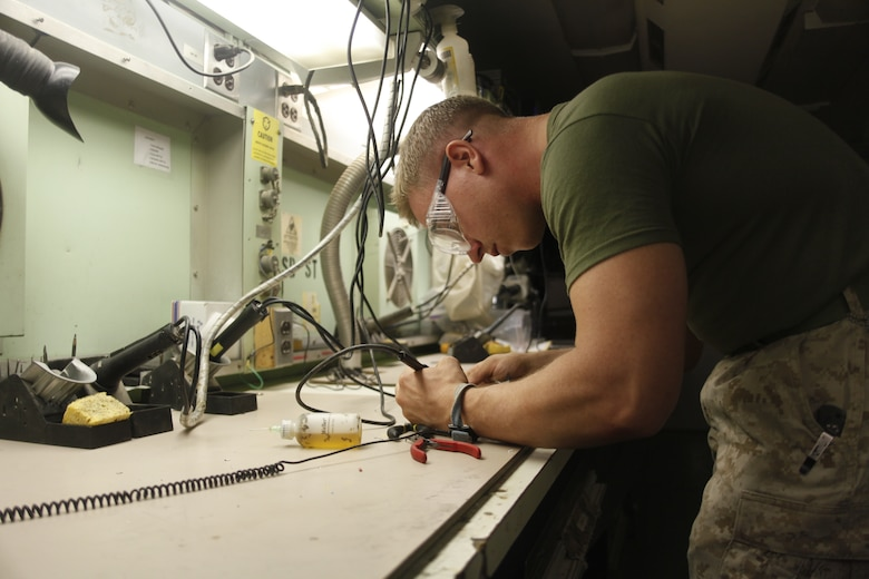 Sgt. George Thorpe, a native of Miami, repairs wires with a soldering tool  at Camp Bastion, Afghanistan, July 6. Thorpe is a micro miniature repair technician with Marine Aviation Logistics Squadron 40.