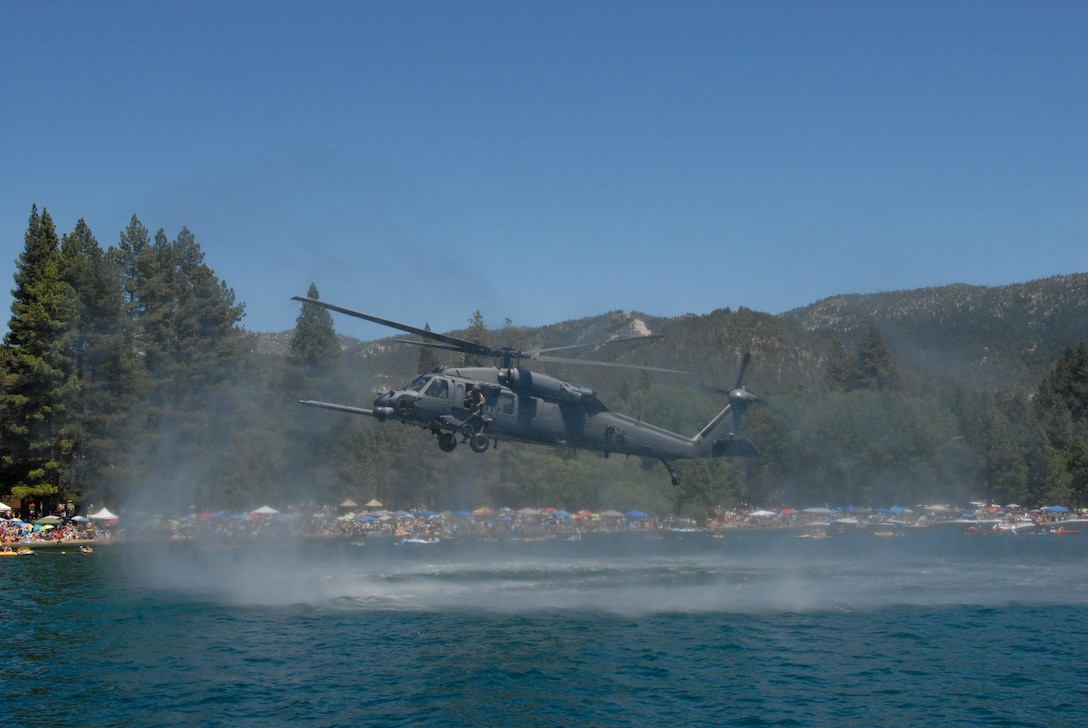 """An HH-60G Pave Hawk helicopter from the California Air National Guard's 129th Rescue Wing performs a low flyover above Lake Tahoe during a rescue simulation near Incline Beach, Nev. on July 3. Members from the 129th Rescue Wing, stationed at Moffett Federal Airfield, Calif., participated in Lake Tahoe's fifth annual Red White and Tahoe Blue 4th of July celebration in Incline Village by providing a live aerial demonstration utilizing the wing's MC-130P Combat Shadow fixed-wing four-engine aircraft, HH-60G Pave Hawk rescue helicopter and """"Guardian Angel"""" pararescuemen. (Air National Guard photo by Senior Airman Jessica Green)"""