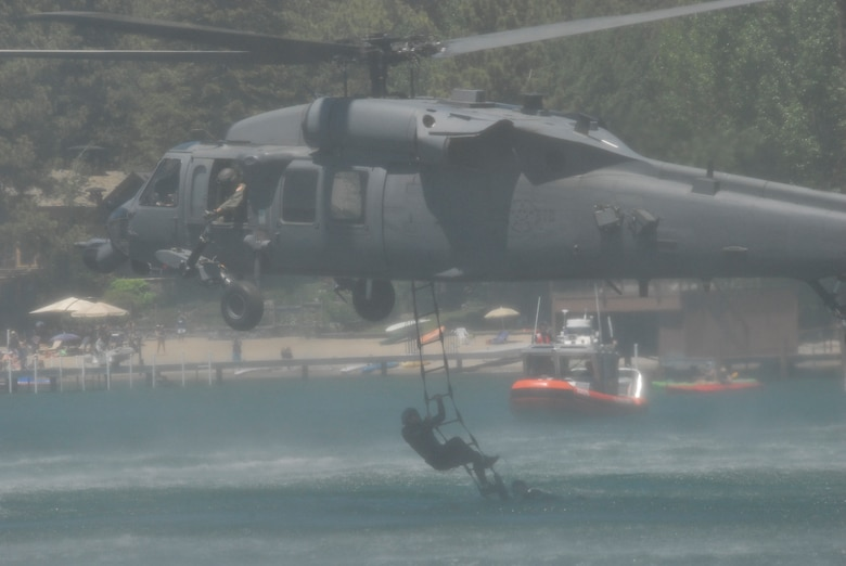 "Pararescuemen assigned to the California Air National Guard's 131st Rescue Squadron climb a rope ladder into an HH-60G Pave Hawk helicopter during a rescue simulation near Incline Beach, Nev. on July 3. Members from the 129th Rescue Wing, stationed at Moffett Federal Airfield, Calif., participated in Lake Tahoe's fifth annual Red White and Tahoe Blue 4th of July celebration in Incline Village by providing a live aerial demonstration utilizing the wing's MC-130P Combat Shadow fixed-wing four-engine aircraft, Pave Hawk rescue helicopter and ""Guardian Angel"" pararescuemen. (Air National Guard photo by Senior Airman Jessica Green)"