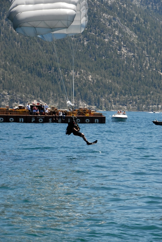 "Staff Sgt. Mickey Chan, a pararescueman assigned to the California Air National Guard's 131st Rescue Squadron, prepares to land in Lake Tahoe after parachuting from 5,000 feet out of an MC-130P Combat Shadow to perform a simulated rescue near Incline Village, Nev. on July. Members from the 129th Rescue Wing, stationed at Moffett Federal Airfield, Calif., participated in Lake Tahoe's fifth annual Red White and Tahoe Blue 4th of July celebration in Incline Village by providing a live aerial demonstration utilizing the wing's MC-130P Combat Shadow fixed-wing four-engine aircraft, HH-60G Pave Hawk rescue helicopter and ""Guardian Angel"" pararescuemen. (Air National Guard photo by Senior Airman Jessica Green)"
