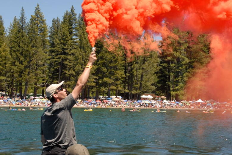 "Master Sgt. Seth Zweben, a pararescueman assigned to the California Air National Guard's 131st Rescue Squadron, pops a smoke flare to identify the recovery site to the four-man pararescue team parachuting from the MC-130P Combat Shadow flying overhead during a rescue demonstration near Incline Beach, Nev. on July 3. Members from the 129th Rescue Wing, stationed at Moffett Federal Airfield, Calif., participated in Lake Tahoe's fifth annual Red White and Tahoe Blue 4th of July celebration in Incline Village by providing a live aerial demonstration utilizing the wing's Combat Shadow fixed-wing four-engine aircraft, HH-60G Pave Hawk rescue helicopter and ""Guardian Angel"" pararescuemen. (Air National Guard photo by Senior Airman Jessica Green)"
