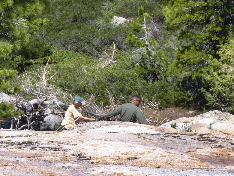 Senior Airman Edward Drew assists a hiker during a rescue mission in El Dorado National Forest, Calif., July 4, 2011.  An aircrew from the 129th Rescue Wing rescued the hiker after she was missing for nearly 48 hours.  (California Air National Guard photo by Staff Sgt. Andrew Gibson)