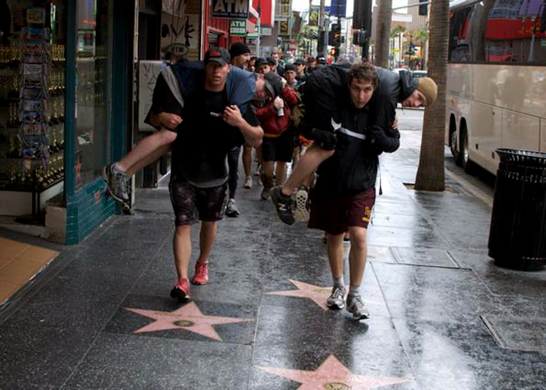 "Participants in the GORUCK Challenge in Los Angeles buddy-carry each other down Hollywood's ""Walk of Fame"" as a feat in the challenge. Edwards Airmen 1st Lt. Paul Issler from the 412th Test Management Division and 1st Lt. Erin Wallace, 773rd Test Squadron, competed in the rucksack march through the city. The challenge involved performing calisthenics and carrying weight on their back for more than 12 hours. (Courtesy photo)"