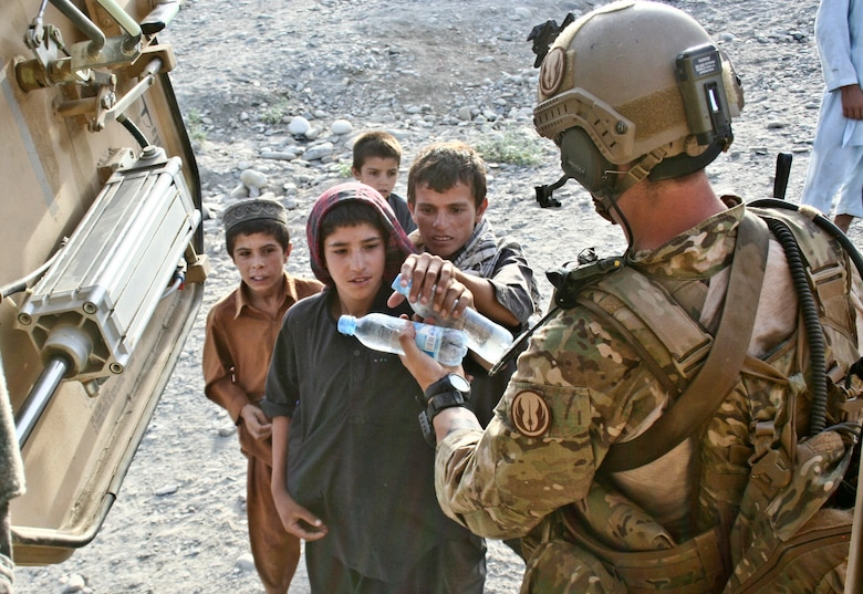Senior Airman Michael McAffrey gives Afghan children bottles of water after completing a mission in Khanda Village in Laghman province, Afghanistan, June 18, 2011. Airman McAffrey is a joint terminal attack controller with the Washington Air National Guard's 116th Air Support Operations Squadron. (Courtesy Photo)
