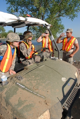 DAKOTA DUNES, S.D. - Sgt. Stephanie Johnson (left) from Jasper, Minn., a member of Medical Command based out of Rapid City and Master Sgt. Angela Pesicka from Parker, a member of the 114th Fighter Wing, Medical Group, pull up in their all-terrain vehicle to offer water to levee patrol members here June 28.  The South Dakota National Guard Soldiers and Airmen are patrolling the levee to monitor for weaknesses which might allow the flooding Missouri River to break through.  (Photo by Tech. Sgt. Quinton Young)(RELEASED)