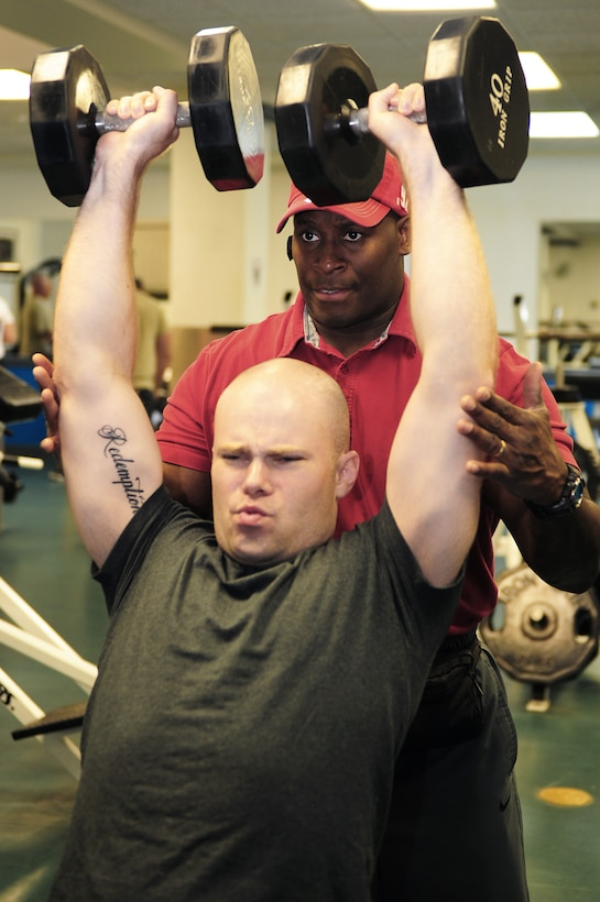 Staff Sgt. David Johnson finishes a lifting set while Omar Acosta spots him. Johnson is a gym operations manager assigned to the 375th Force Support Squadron at Scott Air Force Base, Ill. Acosta is a personal trainer at the Scott AFB gym. (U.S. Air Force photo/Staff Sgt. Teresa M. Jennings)