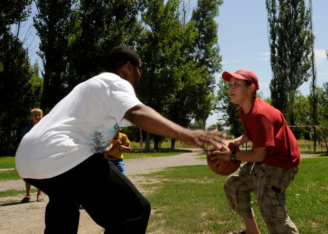 Staff Sgt. Diamond Edwards tries to block the shot of a local child as the two play a game of basketball July 1, 2011, in Kyrgyzstan. After donating a public address system to the village, Airmen from the Transit Center at Manas 376th Expeditionary Communications Squadron played games of basketball, volleyball, American football and Frisbee with village children. Edwards is a communications project manager. (U.S. Air Force photo/Tech. Sgt. Tammie Moore)
