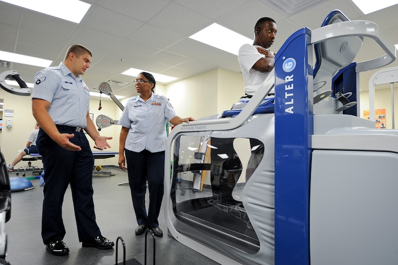 SEYMOUR JOHNSON AIR FORCE BASE, N.C. – Physical therapy technician Senior Airman Randy Slaba talks with medical services flight chief and licensed practical nurse Tech. Sgt. Nina Anderson, both from the 4th Medical Operations Squadron, about the new Alter-G Anti-Gravity Treadmill here June 20, 2011. Senior Airman Robert Glenn, 567th Red Horse Squadron, also cools down on the treadmill during a physical therapy session for his injured ankle. The treadmill prevents injury by filling with air around the body to reduce impact on the joints. Slaba hails from North Platte, Neb. and Anderson hails from Fayetteville. (U.S. Air Force photo by Tech. Sgt. Colette M. Graham/Released)