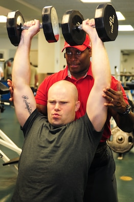 SCOTT AIR FORCE BASE, Ill. -- Staff Sgt. David Johnson, James Gym operations manager, finishes a lifting set while Omar Acosta, a personal trainer working at the James Gym, spots him. Mr. Acosta has been a personal trainer, power lifter and body builder for more than 30 years and is available to help military members improve their fitness. (U.S. Air Force photo/ Staff Sgt. Teresa M. Jennings)