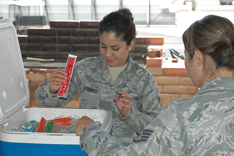 Senior Airman Iana Gutierrez accepts a frozen popsicle from Staff Sgt. Charmaine Pozo, secretary, Junior Enlisted Council, July 8. The frozen treats boosted moral for wing members working in the 100 degree Tucson heat. (U.S. Air Force photo/Staff Sgt. Jordan Jones)