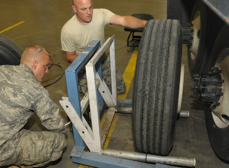 Senior Airman Tobias Burrier (left) and Staff Sergeant Jeffrey Strong (right) from Vehicle Maintenance, Logistics Readiness Squadron, 146th Airlift Wing, Channel Islands Air National Guard Station, Calif. maneuver a tire onto a large dump truck during a deployment to Joint Base Elmendorf Richardson on June 8, 2011. The 146th AW sent three squadrons to JBER from June 4 to June 18, 2011. The Air Terminal Operations Squadron, Logistics Readiness Squadron, and Security Forces Squadron moved down range to complete their respective annual training requirements. Photo by Tech. Sgt. Alex Koenig