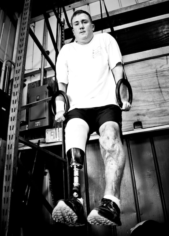 Staff Sgt. David Flowers holds himself up with the parallel rings during a workout June 28, 2011, at Eglin Air Force Base, Fla. The explosive ordnance technician was officially returned to duty in June after he lost his right leg and incurred major damage to his left leg in a land mine explosion in Afghanistan in 2009. In August, he is scheduled to begin training to be an EOD instructor at the Navy EOD School. Flowers is assigned to 366th Training Squadron, Det. 3. (U.S. Air Force photo/Samuel King Jr.)