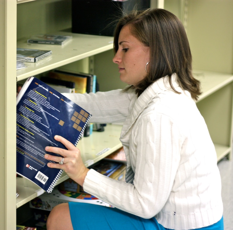 Kate Ruping, loan locker manager SAMS Place, organizes a bookshelf. SAMS Place, located in Bldg. 144 behind the Airmen and Family Readiness Center, offers a wide variety of items for enlisted service members between the grades of E1-E6. (U.S. Air Force photo/Whitney Haskell)