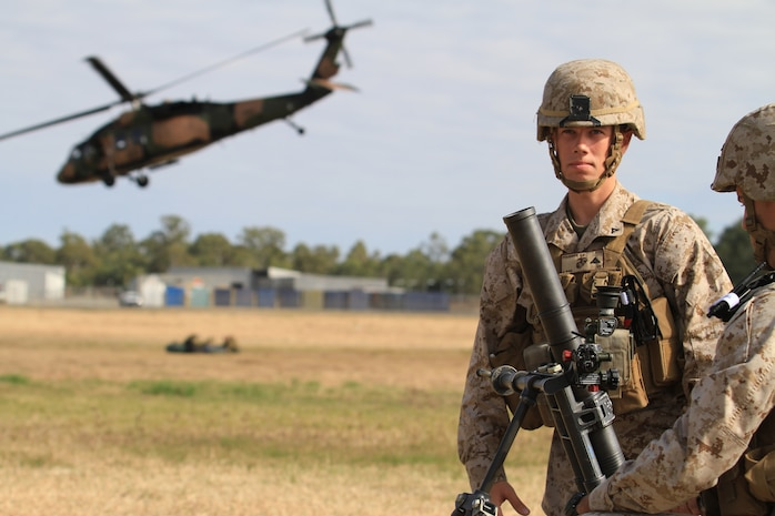 U.S. Marine Corps Lance Cpls. Stephan A. Fournier (left) and Craig J. Reyes (right), both mortarmen with Golf Company, Battalion Landing Team 2nd Battalion 7th Marines, 31st Marine Expeditionary Unit, conduct a weapons drill with a 60 mm mortar as an Australian Blackhawk helicopter takes off behind them on Camp Rocky during Talisman Saber 2011. TS11 is a biennial combined training activity, designed to train Australian and U.S. forces in planning and conducting Combined Task Force operations to improve Australian Defense Force/U.S. combat readiness and interoperability. It reflects the closeness of the alliance and the strength and flexibility of the ongoing military-military relationship.