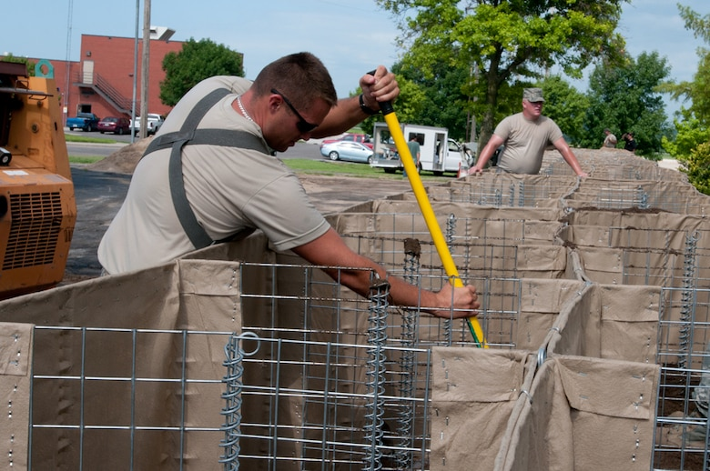 Airmen with the Missouri Air National Guard's 139th Airlift Wing erect HESCO barriers around various buildings at Rosecrans Air National Guard Base, St. Joseph, Mo., July 12, 2011. The sand-filled barriers are being installed as a precautionary measure should the Missouri River breach the levees here. (U.S. Air Force photo by Staff Sgt. Michael Crane/Released)