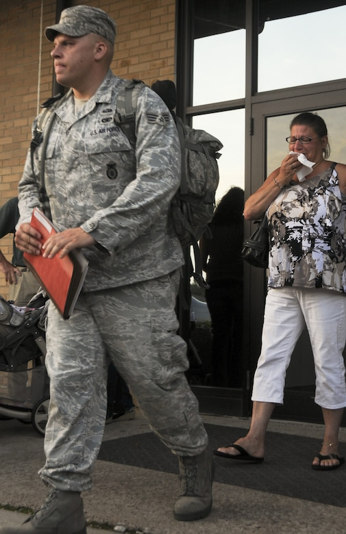 Senior Airman Justin Rogers, a member of the 108th Security Forces Squadron, a New Jersey Air National Guard unit, leaves his family behind as he prepares to board a bus at Joint Base McGuire-Dix-Lakehurst on July 12, 2011. Rogers, along with approximately 30 other security forces members, have deployed to Southwest Asia in support of Operation New Dawn where they will be responsible for maintaining security at the air base. (U.S. Air Force photo/Airman Kellyann Novak)
